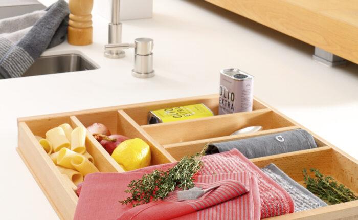 Im Anschnitt ist eine Küche mit Spülbekcne zu sehen mit einem Besteckkasten der dekoriert ist mit trockenen Nudeln, Zitronen, Zwiebeln, Kräutern Ölivenöl-Dosen und dazu dekoriert ein rotes und antrahzitfarbenes Halbleinen Geschirrtuch.