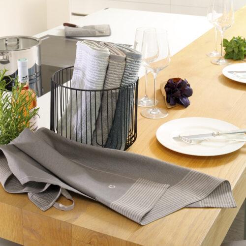 im Anschnitt ist eine Küchenzeile mit Ceranfeld zu sehen. Davor liegt ein Halbleinengeschirrtuch in der Farbe graphit und dahinter stehen in einem schwarzen runden Körbchen drei Küchenfrottiertücher in silber, graphit und anthrazit.