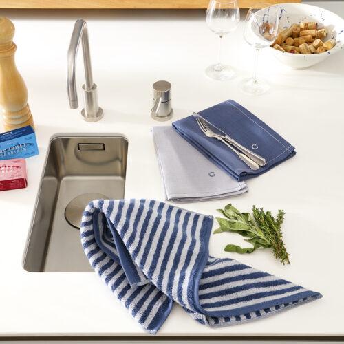 Ein Spülbecken in einer Küche, daneben steht eine Pfeffermühle Weingläser und im Hauptaugenmekr zwei Halbleinen Geschirrtücher in silber und marineblau. Dazu etwas salbei und thymian dekortiert sowie ein marine-silber gestreiftes Küchenfrottiertuch