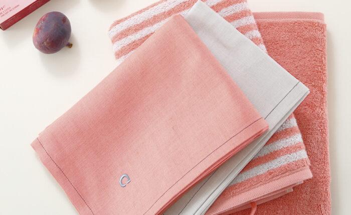 2 Halbleinen Geschirrtücher in der Farbe rouge und silber liegen auf zwei Küchenfrottiertüchern in gestreift rouge und silber und ein einfarbiges in rouge dazu dekoriert sind zwei Feigen